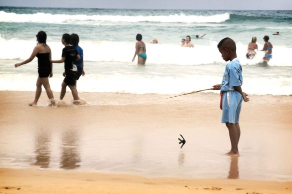 This kid was quietly playing with his toy fish whilst his parents were working hard to sell their ware on the beach